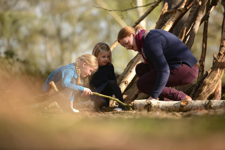 Family investigating under a log