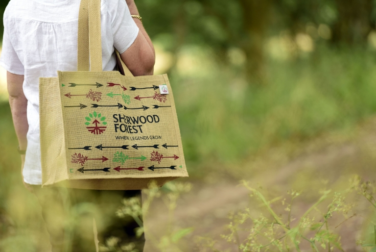 Woman walking through woodland with re-useable bag